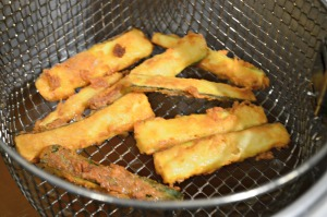 Fry the coated courgettes in hot oil